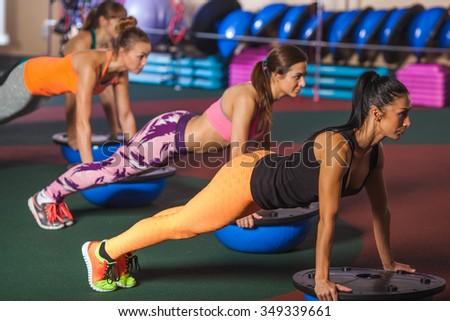 group of female women balancing on bosu ball in push ups position - stock photo