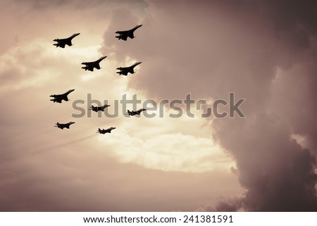 Group of fighter aircraft against a background of pink clouds at sunset