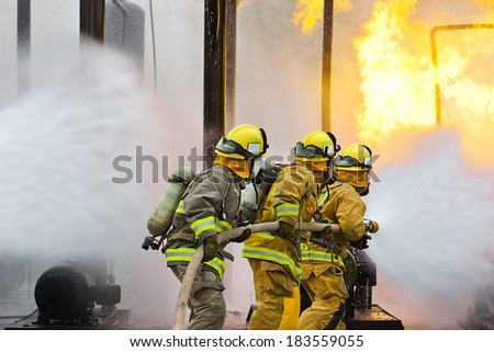 Group of firefighters advance forward putting out a fire. - stock photo