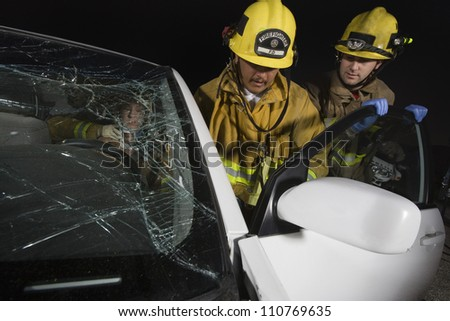Group of firemen standing by car - stock photo
