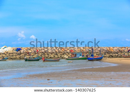 group of fishing boat within rock pier/breakwater - stock photo
