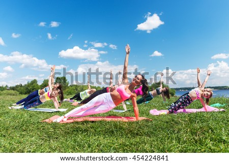 Group of fit girls going side plank exercise in nature on a sunny day. - stock photo