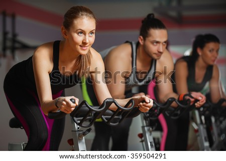 Group of fit people cycling in fitness club - stock photo