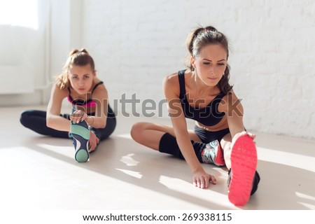 Group of fit women working stretching leg muscles of back to warm up at gym fitness, sport, training and lifestyle concept - stock photo