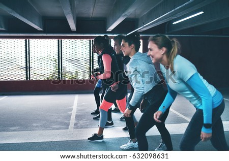 Group of fit young friends working out in a commercial parking lot in town lining up in the starter position for a sprint or race down the interior