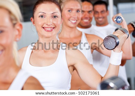 group of fitness people lifting weight in gym - stock photo