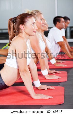 group of fitness people stretching on gym floor - stock photo