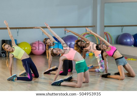 Group of fitness team performing stretching exercise in fitness studio