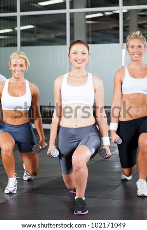 group of fitness woman using dumbbells in gym - stock photo