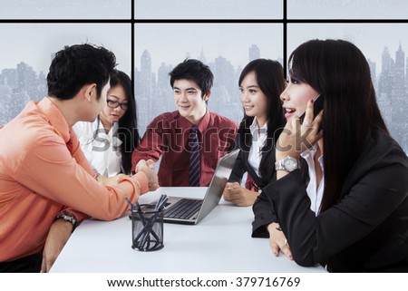 Group of five businesspeople closing a meeting with two businessmen shaking hands in the office - stock photo