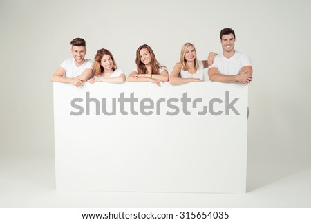Group of Five Cheerful Young Friends Leaning on Large White Poster with Copy Space Against Off-White Wall Background Inside the Studio. - stock photo