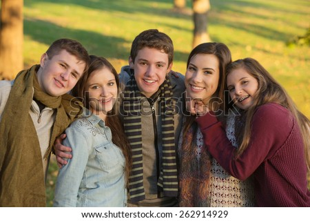 Group of five cheerful youth outdoors embracing - stock photo