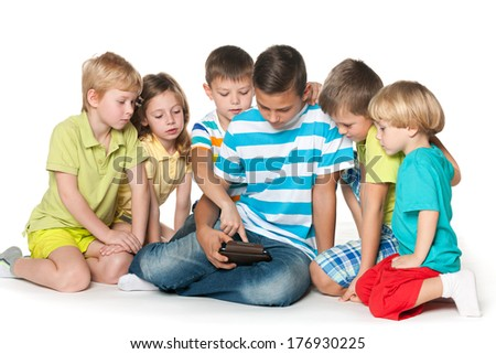 Group of five children are playing with a gadget