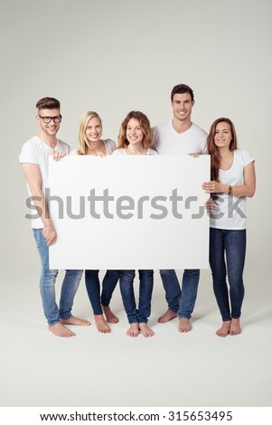 Group of Five Close Best Friends in Casual Outfits, Holding a White Large Poster with Copy Space and Smiling at the Camera. Captured in Studio. - stock photo