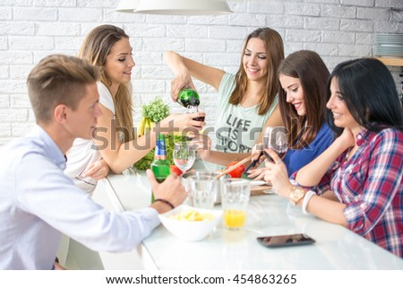 Group of five friends having fun in kitchen. They are drinking red wine and preparing a meal. - stock photo