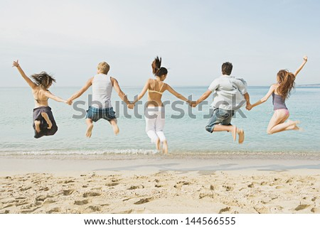 Group of five friends holding hands and jumping at once on the shore of a golden sand beach against a blue sea and sky, expressing energy, fun and joy during their summer vacation. - stock photo