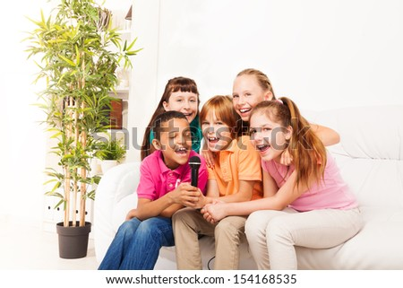 Group of five happy diversity kids, boys and girls, singing together sitting on the coach in living room - stock photo