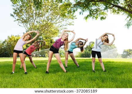 Group of five happy girls doing flexibility exercises