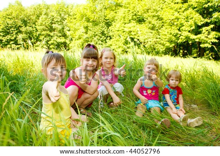 Group of five happy kids sitting in the grass - stock photo