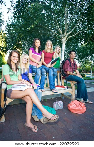 Group of five high school girls and one boy sitting on a bench holding books. Vertically framed photo. - stock photo