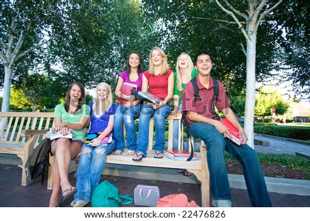 Group of five laughing high school girls and one boy sitting on a bench holding books. Horizontally framed photo.