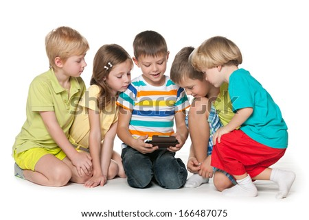 Group of five little children are playing with a new gadget on the floor - stock photo
