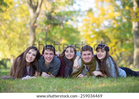 Group of five male and female teens laying down outdoors - stock photo