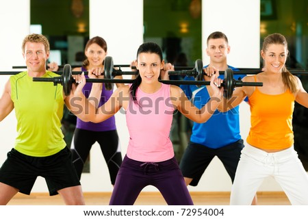Group of five people exercising using barbells in gym or fitness club to gain strength and fitness - stock photo