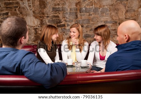 Group of five people having fun in cafe - stock photo