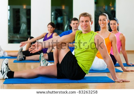 Group of five people is doing stretching exercises in fitness club on gym mats