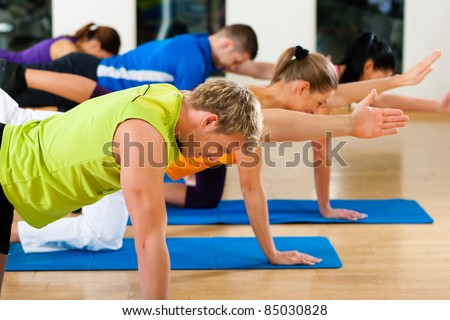Group of five people is doing stretching exercises in fitness club on gym mats - stock photo
