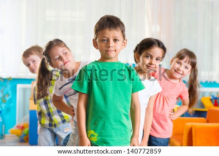 Group of five preschoolers standing in playroom - stock photo
