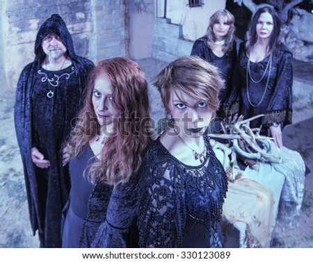 Group of five Satan worshippers near altar outdoors