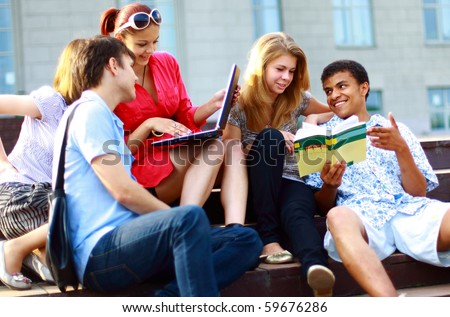 Group of five students outside sitting on steps