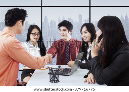 Group of five successful young entrepreneurs closing a deal by shaking hands in the office
