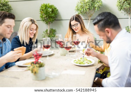Group of five young adults eating lunch in a restaurant terrace and having a good time together