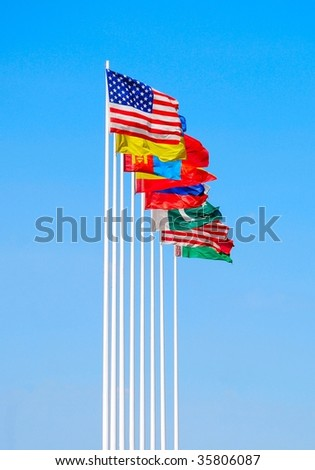Group of flags against blue sky