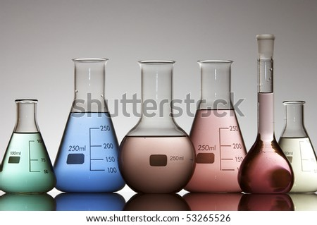 group of flasks of various kinds with colored liquid and a white background