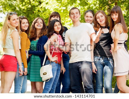 Group of flirting young girls with happy smiling popular boy