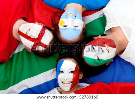 Group of football fans with painted faces lying over the South African flag - stock photo