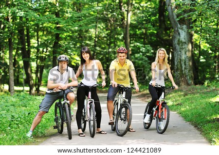 Group of four adults on bicycles in the countryside - stock photo