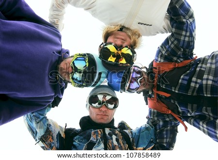 Group of four athletes snowboarders in circle looking down, teamwork concept, low angle shoot - stock photo