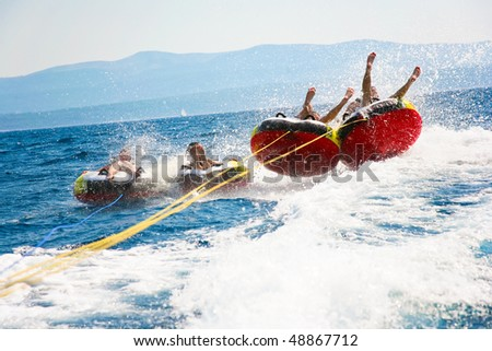 Group of four bouncing up over wake on tubes on Croatian coast - stock photo