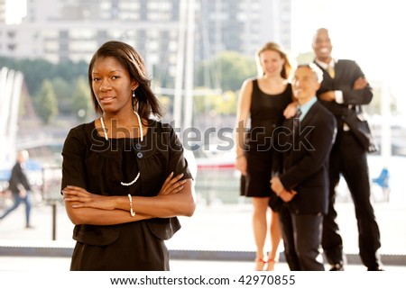 Group of four business people with one woman as focus. Horizontally framed shot.