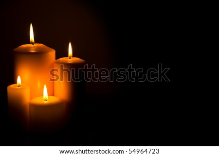 Group of four candles lights  in a side in darkness with copy space for text
