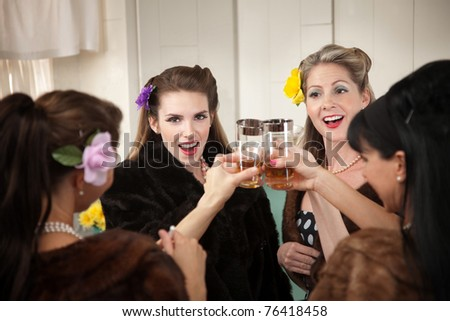 Group of four Caucasian housewives raise a toast in a kitchen - stock photo