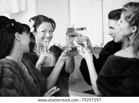 Group of four Caucasian women in a kitchen make a toast - stock photo