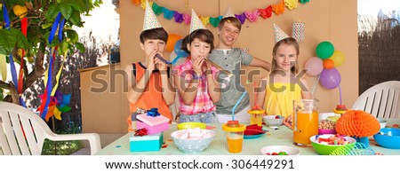 Group of four children at a home garden birthday party having fun and eating sweets and party food and drinking, outdoors. Kids at party with paper hats and party blowers on sunny day, lifestyle. - stock photo