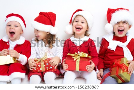 Group of four children in Christmas hat with presents - stock photo