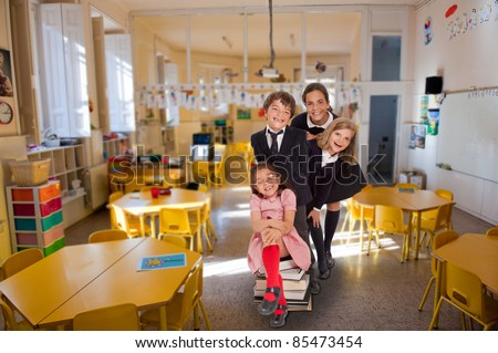 Group of four children of different ages having fun in a classroom - stock photo